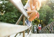 Jeune femme s'asseyant sur une balustrade de pont dans des espadrilles de jeans Photo stock
