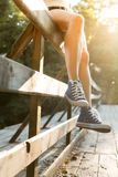 Jeune femme s'asseyant sur une balustrade de pont dans des espadrilles de jeans Images stock