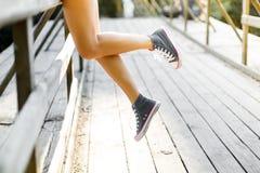 Jeune femme s'asseyant sur une balustrade de pont en bois dans des espadrilles de jeans Photographie stock libre de droits