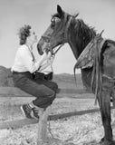 Jeune femme s'asseyant sur une barrière et alimentant son cheval (toutes les personnes représentées ne sont pas plus long vivante Photos libres de droits