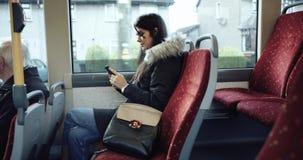 Jeune femme s'asseyant sur une chaise et à l'aide du smartphone dans l'autobus 4K banque de vidéos