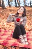 Jeune femme s'asseyant sur une couverture et tenant une grande tasse rouge Photographie stock libre de droits