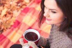 Jeune femme s'asseyant sur une couverture et un thé potable Images stock
