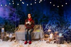 Jeune femme s'asseyant sur une oscillation sous les lampes-torches et se tenir Photos libres de droits