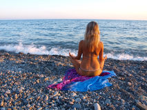 Jeune femme s'asseyant sur une plage pierreuse image stock