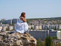 Jeune femme s'asseyant sur une roche photos stock