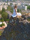 Jeune femme s'asseyant sur une roche photographie stock libre de droits