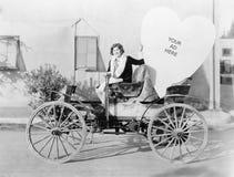 Jeune femme s'asseyant sur une voiture tenant un grand signe en forme de coeur (toutes les personnes représentées ne sont pas plu Photo libre de droits