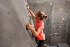 Jeune femme s'exerçant au mur s'élevant d'intérieur de gymnase photo stock
