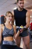 Jeune femme s'exerçant avec des haltères au gymnase image stock