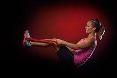 Jeune femme s'exerçant avec la bande élastique de forme physique Image stock