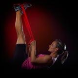 Jeune femme s'exerçant avec la bande élastique de forme physique dans le gymnase Image stock