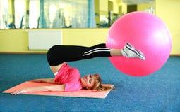 Jeune femme s'exerçant avec la bille de forme physique Photo stock