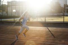 Jeune femme s'exerçant dehors au stade d'athlétisme Photographie stock libre de droits