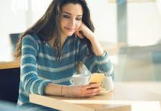 Jeune femme sûre au café utilisant un smartphone Photos stock