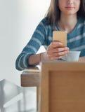 Jeune femme sûre au café utilisant un smartphone Image libre de droits