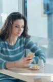 Jeune femme sûre au café utilisant un smartphone Images stock
