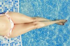 Jeune femme s'étendant par la piscine Image libre de droits