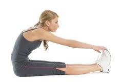 Jeune femme s'étirant pour toucher ses orteils Image stock
