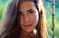 Jeune femme sans maquillage avec de longs cheveux au coucher du soleil Image stock