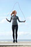 Jeune femme sautant avec la corde de saut dehors Photo stock