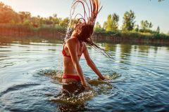 Jeune femme sauter de bikini de l'eau et en faisant l'éclaboussure Vacances d'?t? photo stock