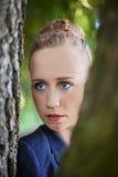 Jeune femme scrutant par des troncs d'arbre Image stock