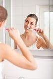 Jeune femme se brossant les dents devant un mirro Image stock