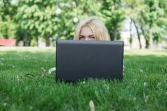 Jeune femme se cachant derrière un ordinateur portatif Photographie stock libre de droits
