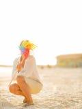 Jeune femme se cachant derrière le jouet coloré de moulin à vent Photo stock