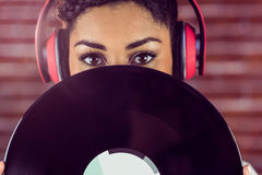 Jeune femme se cachant derrière le vinyle Image libre de droits