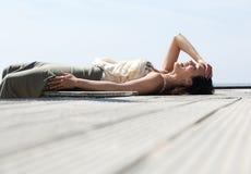 Jeune femme se couchant et riant dehors Photographie stock libre de droits