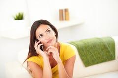 Jeune femme se demandant tout en parlant au téléphone portable Image libre de droits