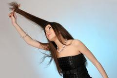 Jeune femme se peignant le cheveu Photo libre de droits