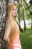 Jeune femme se penchant contre le bouleau dans la forêt Photo libre de droits