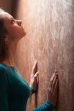 Jeune femme se penchant contre le mur Image libre de droits
