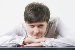 Jeune femme se penchant sur la table Photo stock