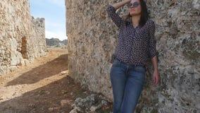 Jeune femme se penchant sur un vieux mur texturisé banque de vidéos