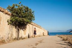 Jeune femme se réveillant à côté du mur avec un arbre et de la mer à l'arrière-plan Photo libre de droits