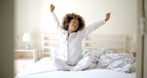 Jeune femme se réveillant sur le lit image stock