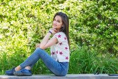 Jeune femme se reposant en stationnement images stock
