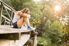 Jeune femme se reposant sur un pont en bois dans des espadrilles de jeans Photos stock