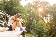 Jeune femme se reposant sur un pont en bois dans des espadrilles de jeans Images stock