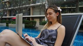 Jeune femme se situant dans la chaise de plage et à l'aide de l'ordinateur portable près de la piscine banque de vidéos
