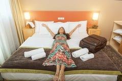 Jeune femme se situant dans le lit d'une chambre d'hôtel Photo libre de droits