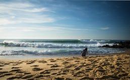 Jeune femme se tapissant sur la plage sablonneuse du rivage atlantique prenant des photos des surfers Image stock