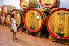 Jeune femme se tenant à côté des barils en bois à un établissement vinicole dans Monta images stock