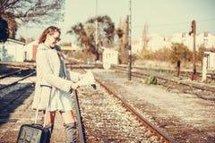 Jeune femme se tenant à la station de train et recherchant ci Photo stock