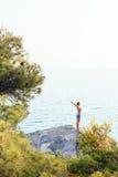 Jeune femme se tenant au bord de la falaise photos stock