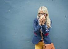 Jeune femme se tenant au mur dehors et buvant une tasse de café photos libres de droits